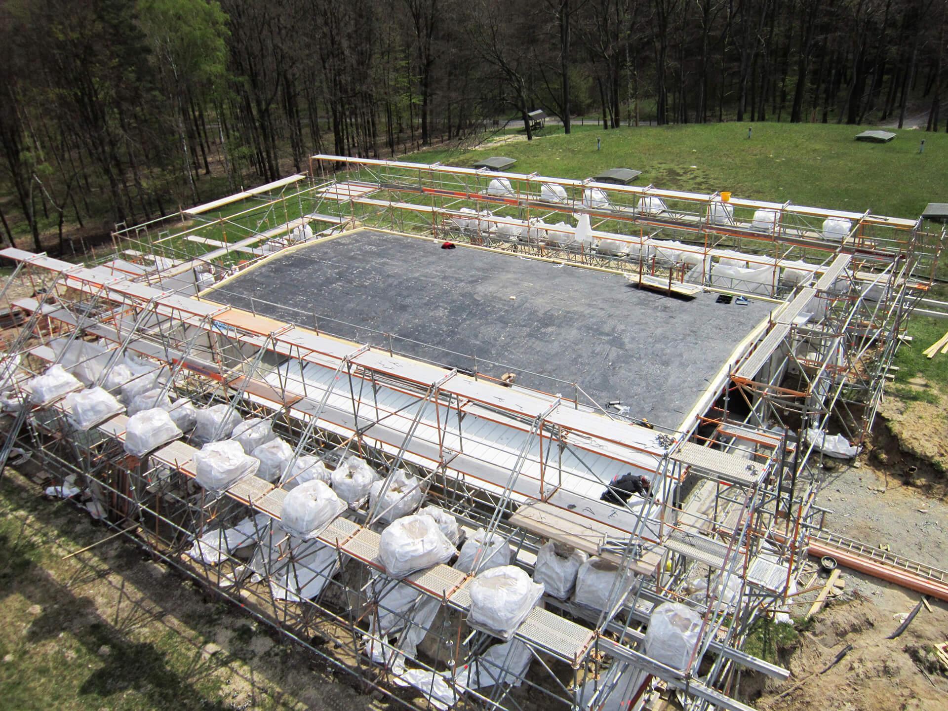 Abdichtung des Dachs am Neubau des Schiebergebäudes mit teilabgebautem, durch Gewichte gegen Sturm gesicherten Schutzgerüst