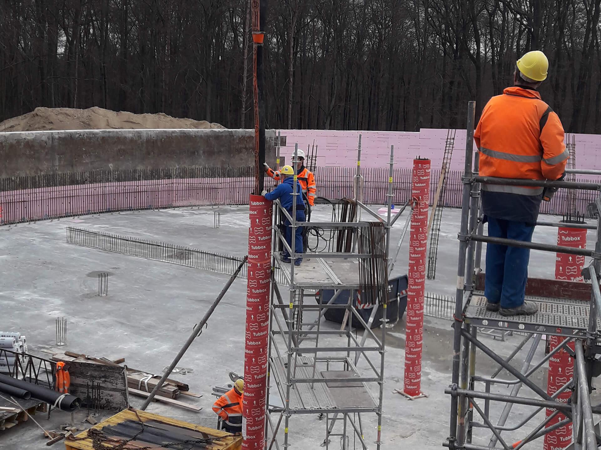 Betonieren der Stützen: Der Beton wird in die Papierhülsen eingefüllt, die präzise ausgerichtet und stabilisiert sind.